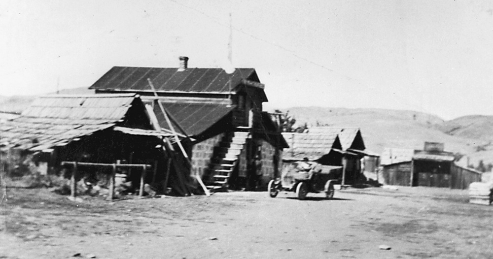 Black and white image of the Kam Wah Chung store with care parked in front, from the early 1900s
