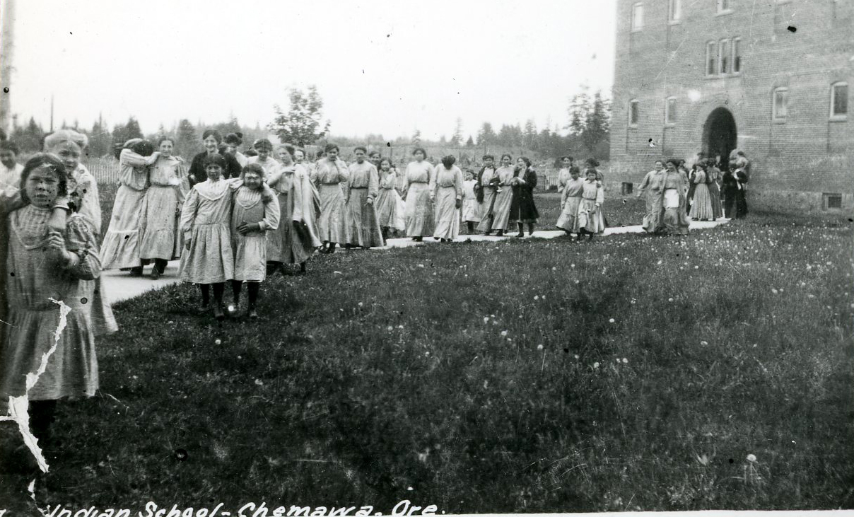 Miss Allie Picard (teacher) and students on Chemawa walkway. Courtesy Oregon Hist. Soc. Research Lib., Orhi62660.