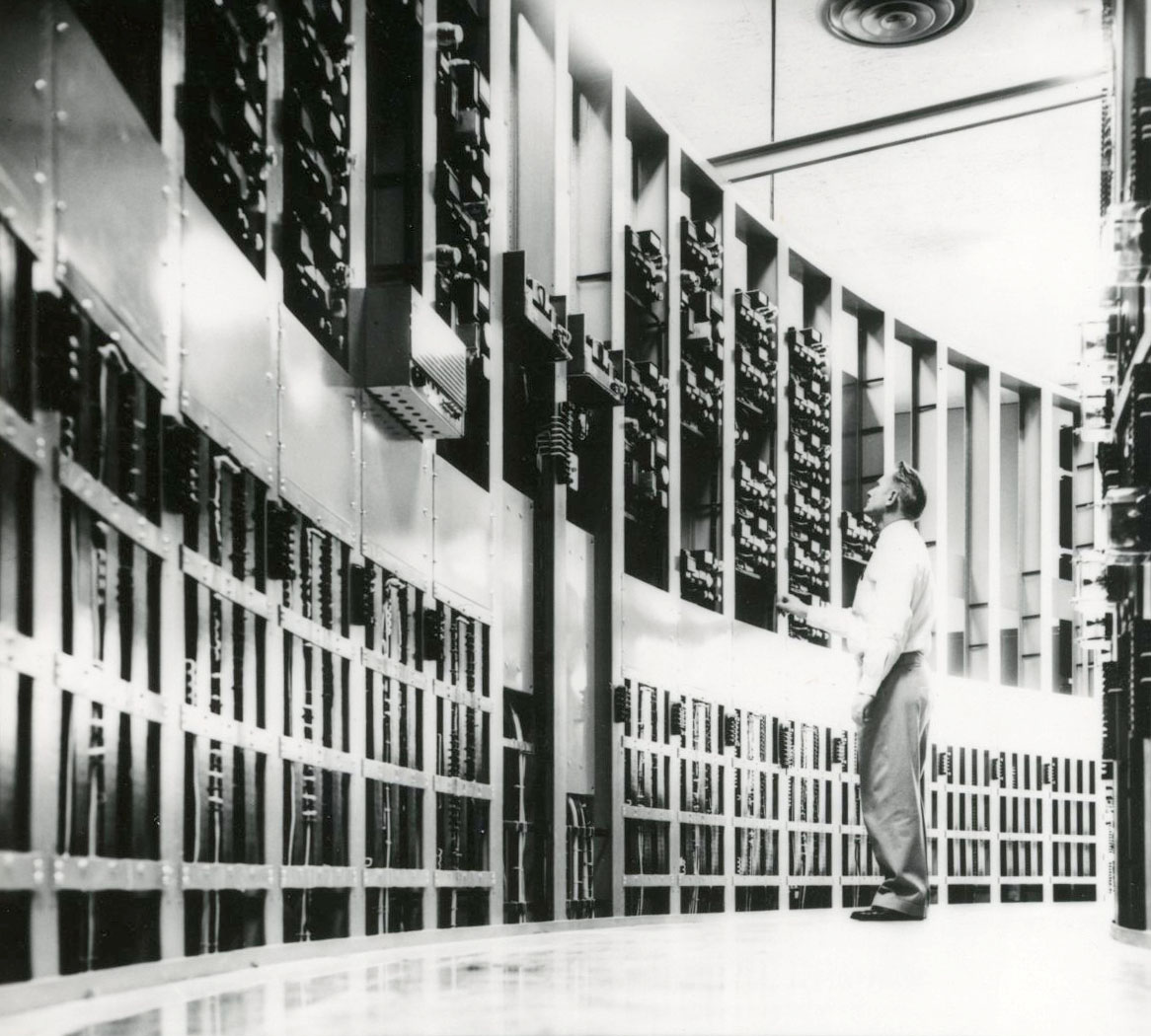 Dispatcher at BPA nerve center inspects bank of electrical relays, 1955